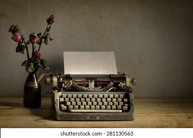Still life with old typewriter with dry rose flowers on wooden  table