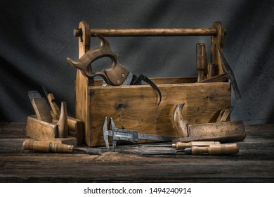 Still life - Old Wooden vintage toolbox with hammers, saw, chisels, plane, slide gauge and pliers in carpentry