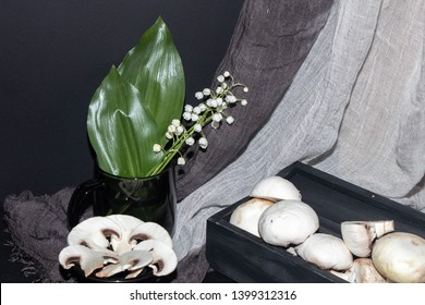 Still life on a black background is a box with white mushrooms, champignons, in the background is a cup of black glass, and there are lilies of the valley in it. In the background hangs a gray fabric.