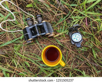 Still life on a theme of tourism on a grass in wood. binoculars. a cup. compass. grass.