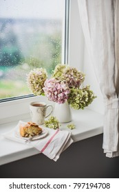 still life on the window - a bouquet of hydrangea in vase and tea with an apple pie