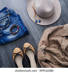 Still Life of Outfit of Womens. Casual jeans outfit with hat and beige shoes and linen shirt on black wooden background.