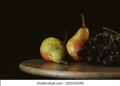 still life pears and black grapes on a black background