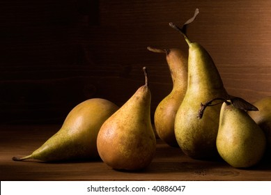 still life with pears on wooden table over an wooden wall