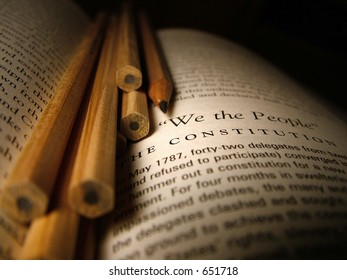 Still life of pencils and a book on the writing of the constitution.