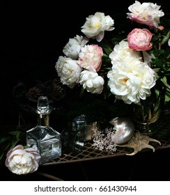 Still life with peonies .silverware and glass, black background