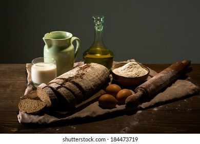 Still life photo of bread and flour with milk and eggs at the wooden table