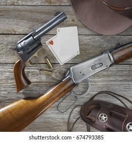 Still life photo of a Colt 45 replica and a Winchester 30-30 with old west props.