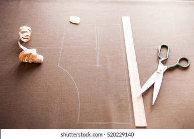 Still life photo of a suit pattern template with tape measure, chalk and scissors. Sewing and tailoring tools and accesories.