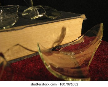 Still life photograph with book and broken glass.