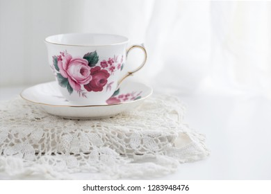 Still life photograph of a white teacup with red roses on a white and bright background