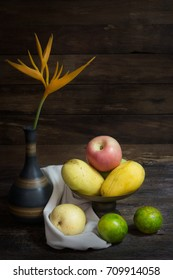 still life photography with apple, oranges, mango and yellow flower in jar on wood