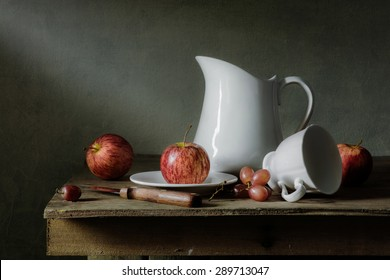 Still life photography with apples, grapes and tableware on wood table