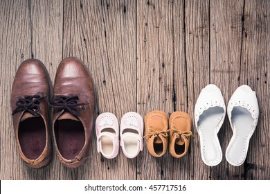still life photography : father mother son and daughter shoes on old wood floor, family concept