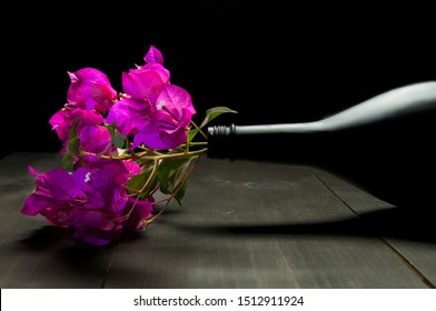 Still life photography, flowers Bugambilias in a black bottle on a rustic wooden table in horizontal position