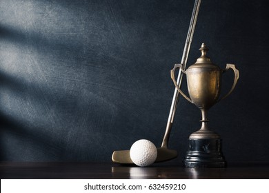 still life photography :  golf club (putter) and ball with old trophy on wood table against art dark background with window light at left