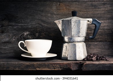 still life photography : old espresso maker with coffee beans and  white coffee cup on old wooden shelf