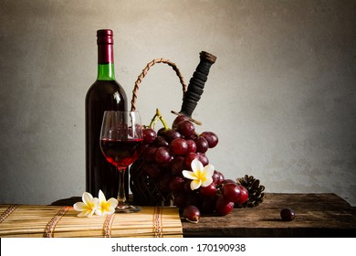 Still life Photography with Old red wine on wooden table and blue grunge background