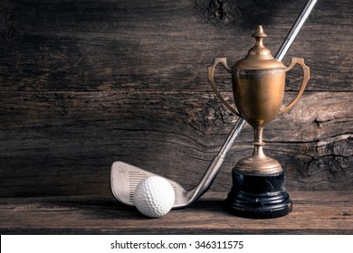 still life photography : old trophy with golf club and ball on old wood