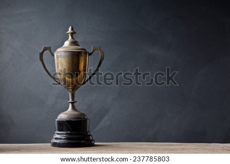 still life photography :  old trophy on old wood with space of art dark background