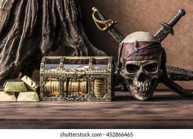 still life photography with pirate skull holding two swords and treasure coffer, gold bar,  bullion. Halloween concept