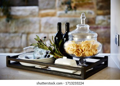 Still life photography styled decorative arrangement on a kitchen bench of a tray with various homewares, wine bottles and food