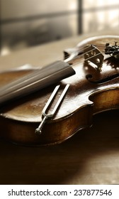 Still life photography of violin and tuning fork