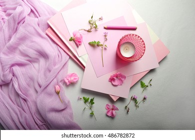 Still life of pink items. Candle holder, scarf, books, pencil and sheets of paper are shot from above. Top view of pink petals and flowers on white fabric.