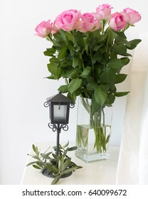 still life pink roses in a glass vase, candle holder lantern, olive tree and white wooden chair