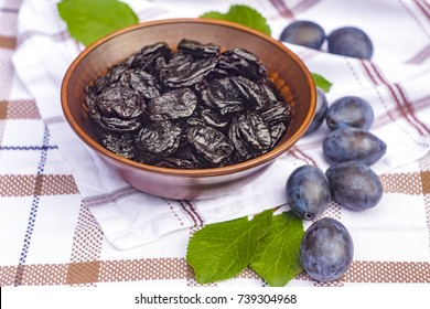 Still life with plums and prunes in a ceramic bowl on the table. Prune and harvest of fresh plums. Plums, prunes and green leaves.