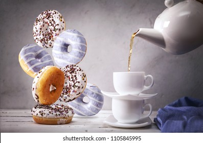 Still life with of the pouring into cap tea and falling down donuts