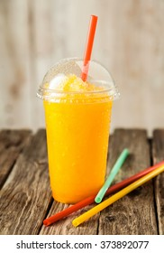 Still Life Profile of Refreshing and Cool Bright Orange Slush Drink in Plastic Cup with Lid Served on Rustic Wooden Table with Collection of Colorful Drinking Straws