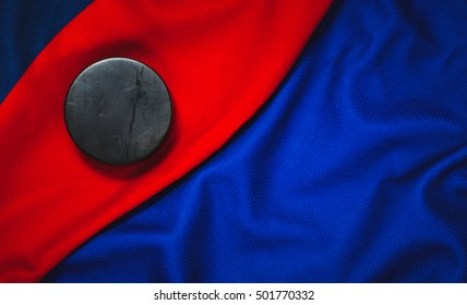 Still life puck on a dark blue and red jersey as a sport background. Ice hockey season concept closeup, top view.