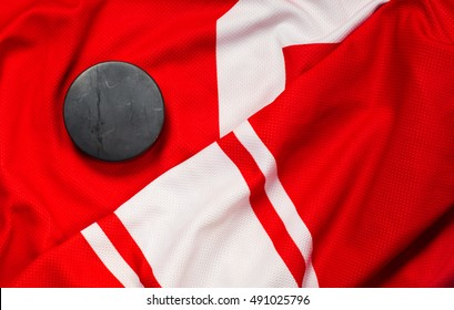 Still life puck on a red and white jersey as a sport background. Ice hockey season concept close up, top view.