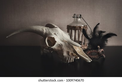 Still life with ram skull, mask and old bottle on dark background