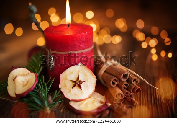 Still life with red advent candle and spices in front of gold bokeh