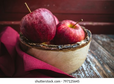 A still life of red apples in a rustic wooden bowl displayed on a wood table.