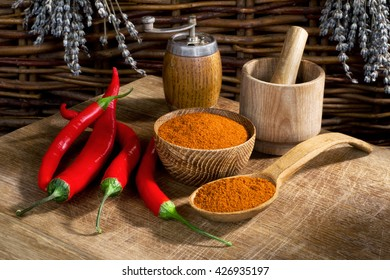 still life with red chili peppers and wooden utensils on the wooden table