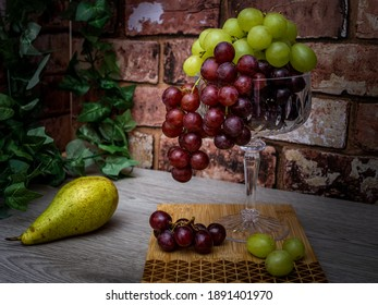 Still life Red, and green grapes in a tall glass with a green pear and wooden board.