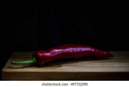 Still life  red pepper on black dark background