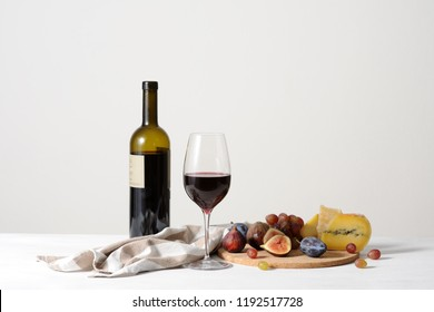still life with red wine, cheese and fruits