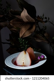 Still life red wine  poached pear with cinnamon stick and rose in white plate on dark background .Yellow pear still life. Yellow quince. Poached quince . Dessert pears in wine. Caramelised pears.