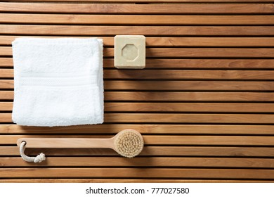 Still life for a refreshing shower, hygiene, bath, sustainable spa or traditional body care concept with solid soap, body brush and pure white towel over beautiful wooden board, copy space wallpaper