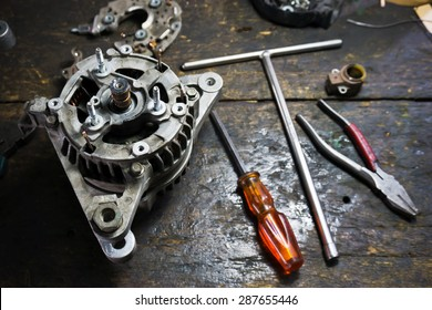 Still life repair of engine parts with Starter car, screwdriver, pliers on old wooden workbench surface.Shallow depth of field.