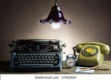 Still life with retro typewriter, alarm clock, telephone and old lantern