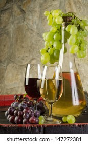 Still life with ripe grapes, wine glasses and wine bottles in old cellar