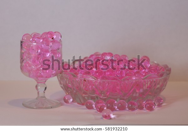 Still life with rose aroma beads in a glass container