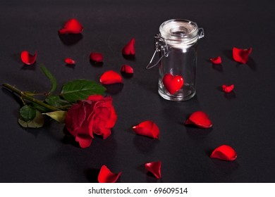 Still life with a rose and a heart in a glass can