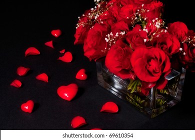 Still life with roses, hearts and petals on black