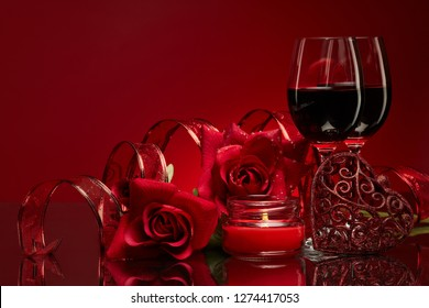 Still life with roses, red hearts and two glasses with wine on a red background. Valentine's Day card with copy space. Design element for romantic greeting card, wedding invitation,